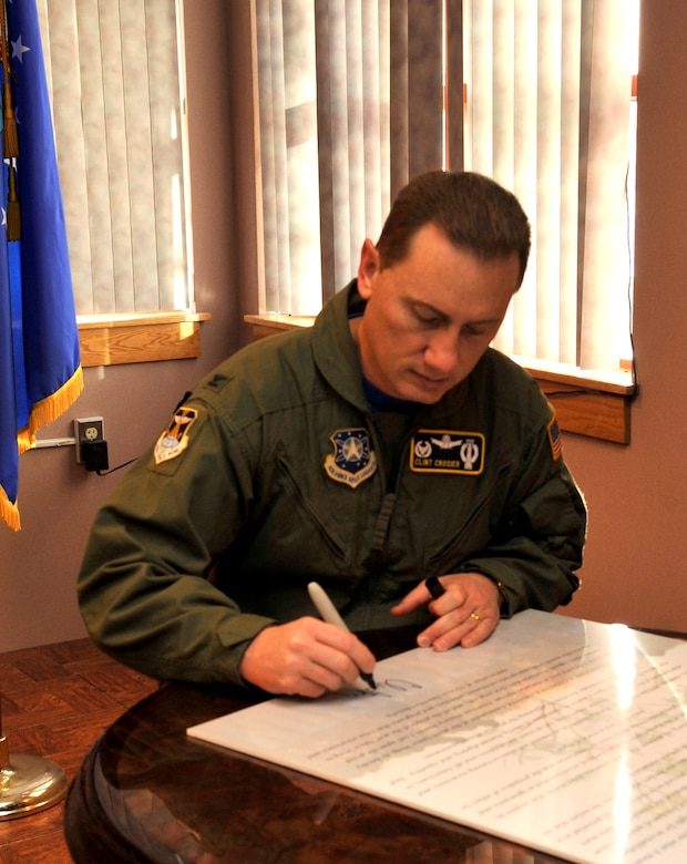 BUCKLEY AIR FORCE BASE, Colo. -- Col. Clinton Crosier, 460th Space Wing commander, signs the Buckley Air Force Base Black History Month Proclamation. a similar proclamation is signed by the President of the United States. (U.S Air Force photo by Airman 1st Class Paul Labbe)