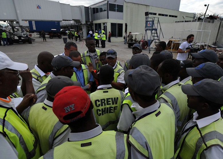 Workers at Toussaint Louverture International Airport in Port-au-Prince, Haiti prepare to receive an American Airlines aircraft. The flight, from Miami, was the first commercial airline flight since a 7.0 magnitude earthquake caused severe damage in and around Port-au-Prince Jan. 12. (U.S. Navy photo by Senior Chief Mass Communication Specialist Spike Call/Released)
