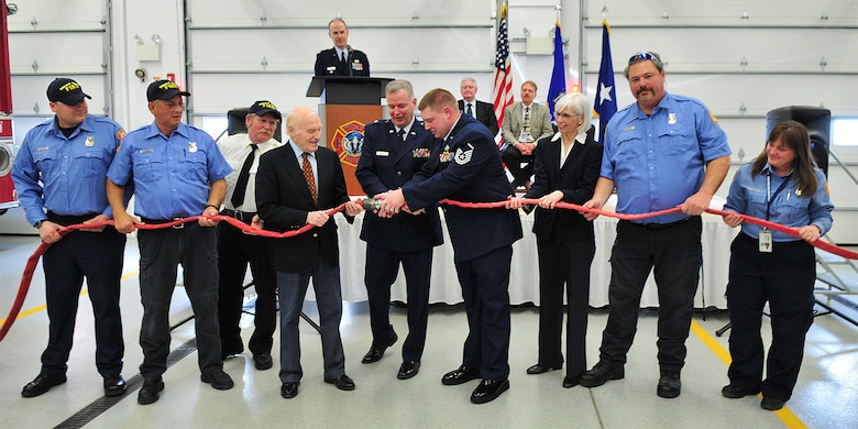 U.S. Sen. Herb Kohl, fourth from left, assists Station Fire Chief Senior Master Sgt. Gary Peck, fourth from right, along with local dignitaries and fire/rescue personnel, to separate a symbolic fire hose during the dedication ceremony of the 115th Fighter Wing airport fire station in Madison, Wis. The expansion and complete renovation of the Wisconsin Air National Guard Fire/Rescue Station at the Dane County Regional Airport was recognized during an official dedication ceremony Feb. 19. Wisconsin Air National Guard photo by Master Sgt. Paul Gorman