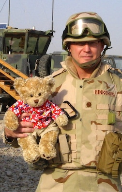 Maj. Mark Binkowski, who passed away Feb. 12 from cancer, is shown here as he holds a stuffed bear he brought with him on deployments to remind him of home. He was assigned to the Air Force Network Integration Center at Scott AFB, Ill., and a memorial service for him was held Feb. 18 at the base.