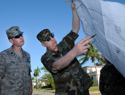 COAST GUARD AIR STATION BORINQUEN, Puerto Rico -- Holding a map to the air station, Chief Master Sgt. Roger Miller, the senior NCO of the Alaska Air National Guard's 176th Civil Engineer Squadron, points out project locations to Lt. Col. Ed Soto, the squadron's commander. A group of 45 squadron members spent two weeks here in early February to train and sharpen their skills on a wide range of infrastructure projects, upgrades and renovations. The squadron undertakes such a mission --  called a Deployment for Training, or DFT -- every year or two. Recent DFTs have taken the squadron's men and women to Israel, Southern California, Hawaii, Ecuador, Okinawa, Minnesota and Texas. AKANG photo by 1st. Lt. John Callahan.
