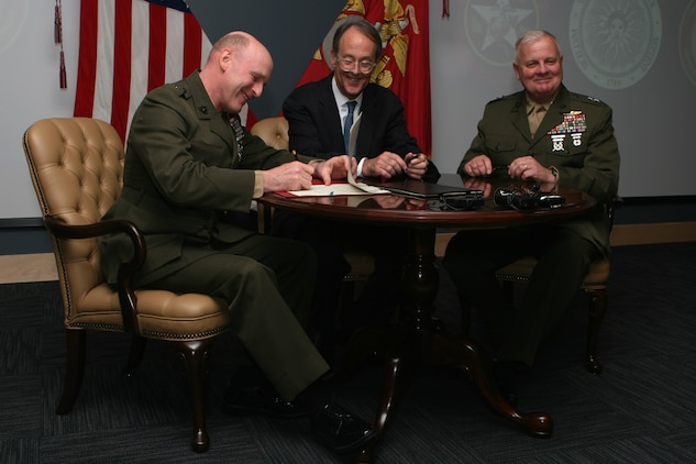 (From left to right) Maj. Gen. Carl B. Jensen, commander of Marine Corps Installations East, Erskine Bowles, the president of University of North Carolina, and Maj. Gen. Paul E. Lefebvre, the commander of U.S. Marine Corps Forces, Special Operations Command, sign two memorandums, which will form a lasting bond between the organizations Feb. 24, at the MARSOC headquarters building auditorium. The memorandums signify a collaborative agreement between three organizations.