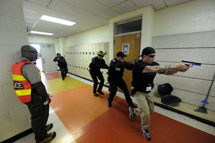 Darrion Holiwell observes as Charleston county aviation authority police prepare to start a hallway clearing exercise during the Active Shooter Training Course at Mt. Pleasant, S.C., Feb. 23, 2010. The AST course prepares first responders on how to react to a hostile situation. Mr. Holiwell is an instructor with AST. (U.S. Air Force photo by James M. Bowman/released)