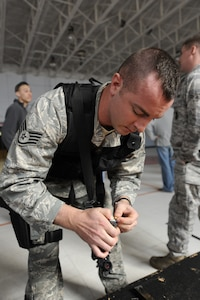 U.S. Air Force Staff Sgt. Brady Frazier loads an M-9 with simunitions prior to starting the Active Shooter Training Course at Mt. Pleasant, S.C., Feb. 23, 2010. The AST course prepares first responders on how to react to a hostile situation. Sergeant Frazier is a security forces member with the 628 Security Forces Squadron at Joint Base Charleston. (U.S. Air Force photo by James M. Bowman/released)