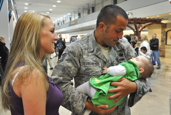 Tech. Sgt. Cody De Los Reyes, 67th Aerial Port Squadron, cradles his 8-month-old daughter as wife, Keri, looks on. Sergeant De Los Reyes returned home Feb. 26 after a month-long deployment to Haiti, where he and 14 other Air Force Reservists from Hill Air Force Base's 419th Fighter Wing helped restore airfield operations at the Toussaint Louverture International Airport in Port-au-Prince. (U.S. Air Force photo/Bryan Magaña)