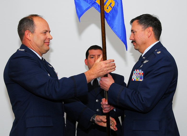 Col. Greg Stroud, 162nd Fighter Wing commander, presents Lt. Col. Eric Kendle, the new 162nd Medical Group commander, the medical group guideon during a change of command ceremony here Feb. 7. (Air Force photo by Master Sgt. Dave Neve)