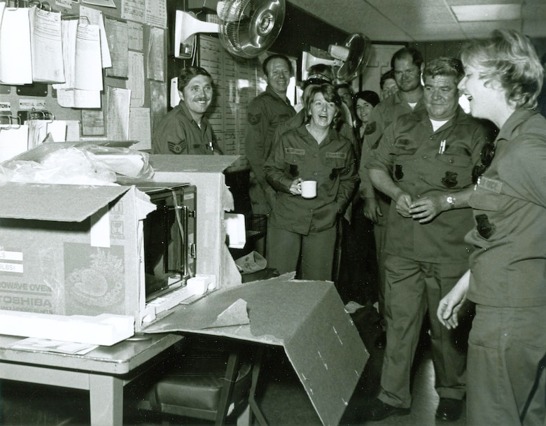 Fellow unit members present a microwave oven to then Staff Sgt. Brenda West in 1983. West's coworkers, trying to lift her spirits after her mother passed away, gathered money for flowers and raised enough to purchase the new oven instead. (Courtesy photo)