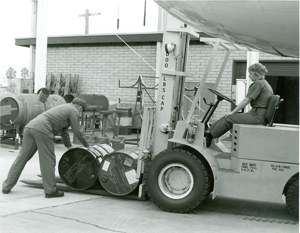 """Master Sgt. John """"Smitty"""" Smith, the first enlistee of the 162nd Fighter Wing, helps then Staff Sgt. Brenda West load a fork lift with barrels of methyl ethyl keytone circa 1983. (Courtesy photo)"""