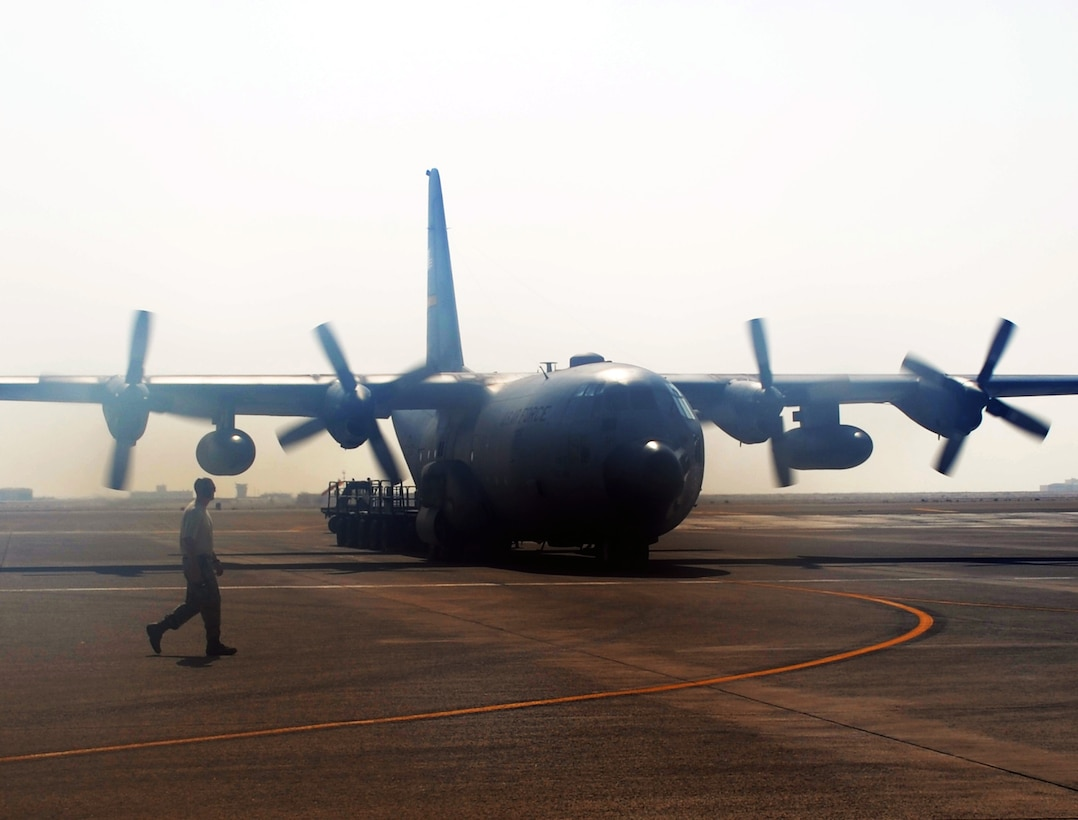 "An Air Force Reserve C-130 Hercules and its crew, along with aerial port Airmen and maintenance Airmen, perform an ""engines running off-load"" at a non-disclosed base in Southwest Asia on Feb. 16, 2010.  The C-130, deployed from the 911th Airlift Wing at Pittsburgh, Penn., is one of the main airlift airplanes used in the U.S. Central Command area of responsibility moving tons of cargo and thousands of people every day. (U.S. Air Force Photo/Master Sgt. Scott T. Sturkol/Released)"