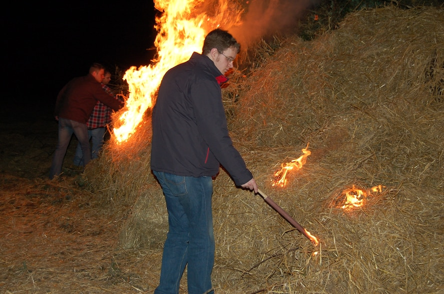 """PREIST, Germany - A young man from the community of Preist lights a bonfire. In the Eifel region, the first Sunday of Lent is called """"Huettensonntag."""" Following an ancient tradition, townsfolk believe the lighting of huge bonfires can chase away winter spirits. The young people of the village build a hut from straw and brushwood that is later set on fire. (U.S. Air Force photo by Iris Reiff)"""