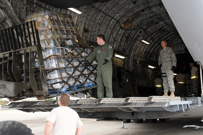 Airmen from the Kentucky Air National Guard?s 123rd Contingency Response Group offload pallets of water, destined for the earthquake victims in Haiti, at anair hub in Barahona, Dominican Republic,  Jan. 25. The hub was established by the Kentucky Guardsmen Jan. 22 to process inbound humanitarian aid. (U.S. Air Force photo by Tech. Sgt. Dennis Flora)