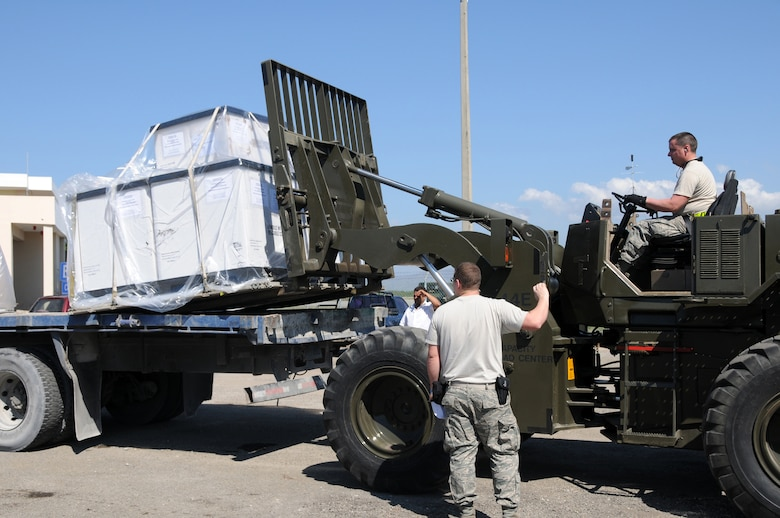 Staff Sgt. Ray Graves from the 123rd Contingency Response Group, Kentucky Air National Guard, loads pallets of water on a truck at an air hub in Barahona, Dominican Republic,  Jan 24. The water is destined to assist earthquake victims in Haiti. (U.S. Air Force photo by Tech. Sgt. Dennis Flora)