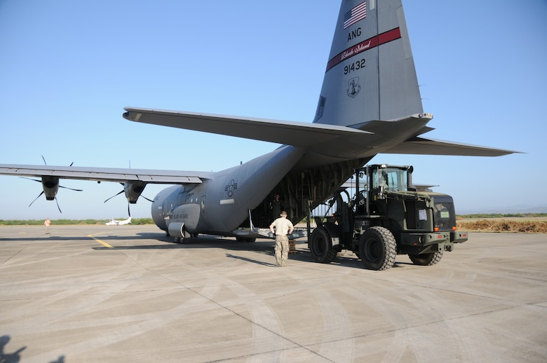 Airmen from the Kentucky National Guard?s 123rd Contingency Response Group unload a Rhode Island C-130 aircraft delivering emergency supplies for the earthquake victims in Haiti at an air hub in Barahona, Dominican Republic,  on Jan. 25. Volunteers and medical professionals from nongovernmental relief organizations are pouring in to the Dominican Republic to help with the wounded Haitian refugees.  The Guardsmen established the air hub Jan. 22 to process inbound humanitarian aid for victims of the earthquake. (U.S. Air Force photo by Tech. Sgt. Dennis Flora)