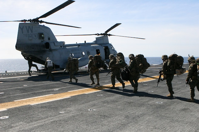 """A CH-46E Sea Knight from Marine Medium Helicopter Squadron (Reinforced), 15th Marine Expeditionary Unit, is loaded with Marines and their gear on the flight deck of USS Peleliu during the 15th MEU's six-month pre-deployment training. The famous """"phrogs"""" of the White Knights have been transporting Marines and Sailors of the White Knights since the Vietnam War era."""