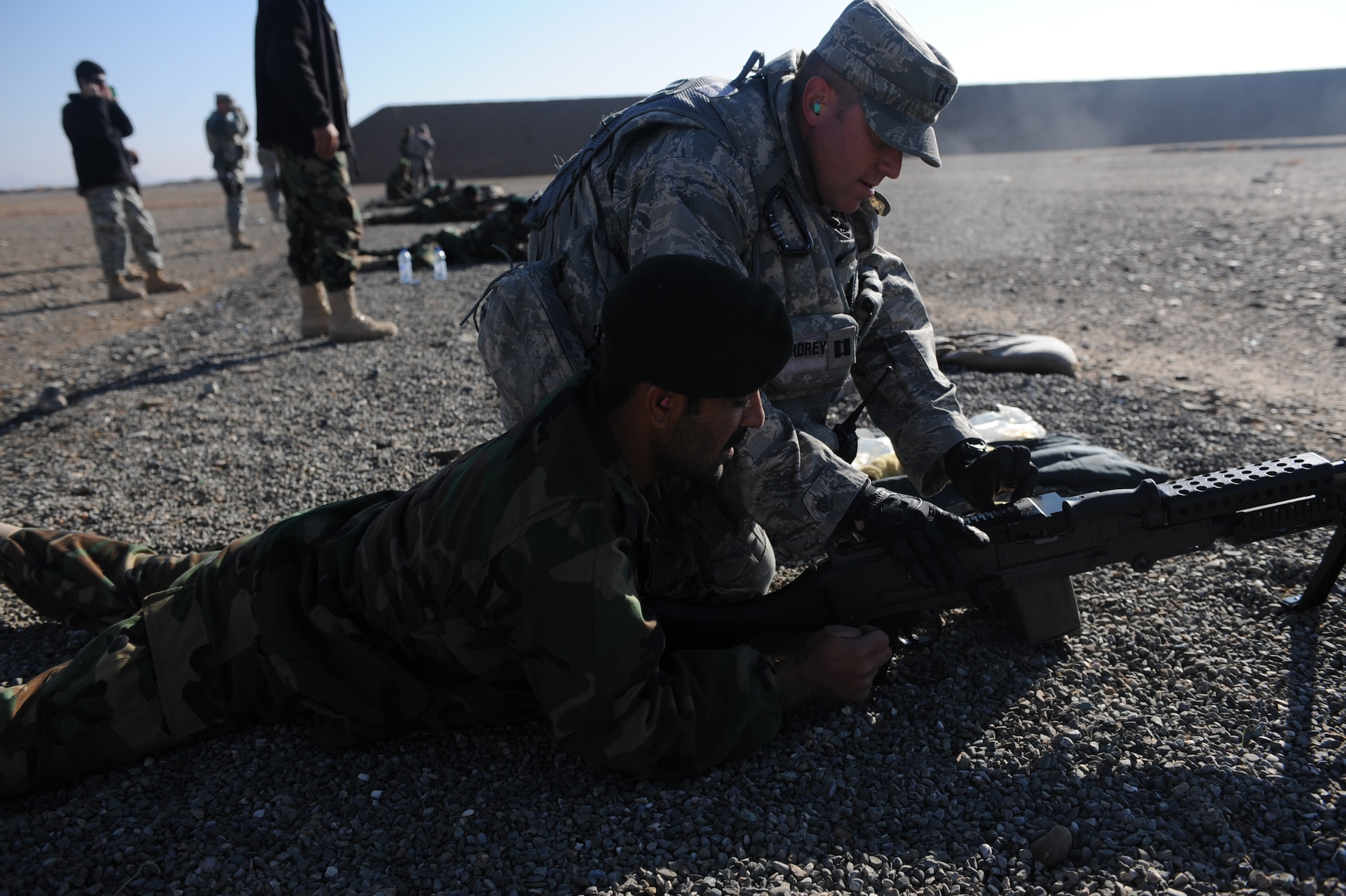 Capt. Shane A. Cordrey, 738th Air Expeditionary Advisory Group lead security forces advisor, shows an Afghanistan National Army Air Corps soldier how to correct an M-240B machine gun malfunction during weapons familiarization training in Kandahar, Afghanistan, Jan. 4, 2010. Captain Cordrey is deployed from Indiana State University where he is an ROTC instructor in support of Operation Enduring Freedom. (U.S. Air Force photo/Staff Sgt. Manuel J. Martinez/Released)