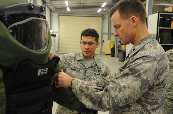 Airman 1st Class Michael Poffenberger poses in an EOD-9 bombsuit while Brig. Gen. Mark C. Dillon, 86th Airlift Wing commander, receives a brief overview on the suit's construction and functionality from A1C Christopher Barajas, 886 Civil Engineer Squadron while visiting the Explosive Ordinance Disposal facility on Ramstein Air Base Germany on December 12, 2009. (U.S. Air Force photo by Tech. Sgt. Sean M. White)