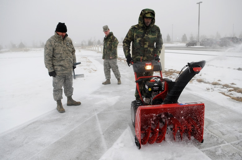 BUCKLEY AIR FORCE BASE, Colo. -- 460th Space Communications Squadron project managers Senior Airman Darnell Walcott, right, Tech. Sgt. Daniel Trigo, left, and Senior Airman Joshua Snook clear the sidewalks Jan 6. Winds here are expected to exceed 40 miles per hour.  (U.S. Air Force photo by Senior Airman Kathrine McDowell)