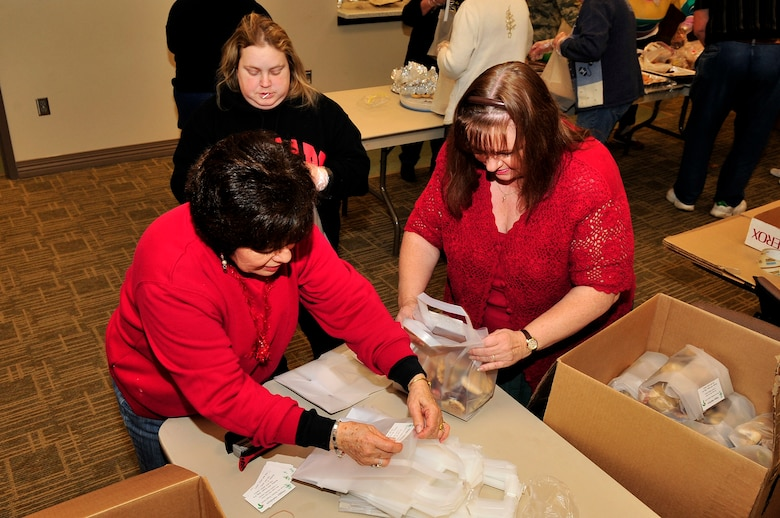 BUCKLEY AIR FORCE BASE, Colo. -- Flo Vennen, Penny Sutton and Debbie Cruz help prepare the finished bags from the cookie caper for delivery at the base chapel Dec. 15, 2009. 154 dozen bags were delivered around the base and to dorm residents. (U.S. Air Force Photo by Airman 1st Class Manisha Vasquez)
