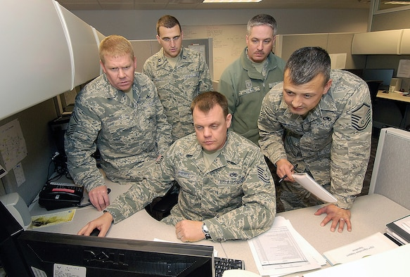 From their newly renovated Tinker home in Bldg. 285, members of the 752nd Operations Support Squadron prepare for a staff assistance visit to Luke Air Force Base, Ariz. Clockwise from front are; Tech Sgt. Wayne Kindrix, Senior Master Sgt. Marcus Jellerson, Capt. Richard Kelley, Master Sgt. Tim White, and Master Sgt. Robert Hipp. (Air Force photo by Margo Wright)
