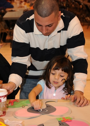 Tech. Sgt. Anthony Valdez, 151st Communications Flight, and his daughter Evangelina, make crafts during the Utah Air National Guard?s annual Children's Christmas Party on December 12. The event included a variety of children?s activities, including face painting, crafts and performing clowns. U.S. Air Force Photo by: Staff Sgt. Emily Monson (RELEASED)