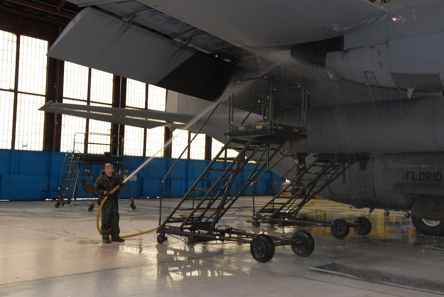 Tech. Sgt. Adam Mace of the 130th Aircraft Maintenance Squadron at Yeager Airport, W.Va. sprays down the underside of a wing on a WC-130H Hercules plane, Friday, Jan. 8, 2010. It took nine hours for a crew of four airmen to soap up, scrub down and spray off the aircraft. Maintenance personnel wash each aircraft twice a year. (U.S. Air Force photo by Staff Sgt. William Hinamon/Released)