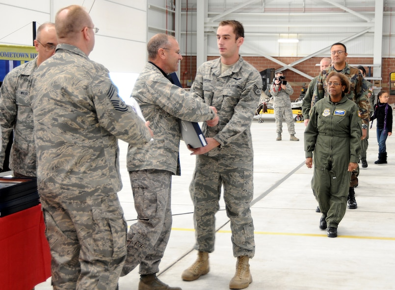 Staff Sgt. Troy Baker is presented with a framed letter and coin by Col. Roger Nye, 167th Airlift Wing commander, during the first Hometown Hero Salute recognition program on Sunday, December 6, 2009. In August 2008, Gen. Craig R. McKinley, chief of the National Guard Bureau, sanctioned the ANG Hometown Heroes Salute recognition program. The purpose of this program is to celebrate and honor Airmen, families, communities and those special supporters who have significantly contributed to supporting our Airmen and ANG?s mission. (U.S. Air Force photo by Msgt Emily Beightol-Deyerle)