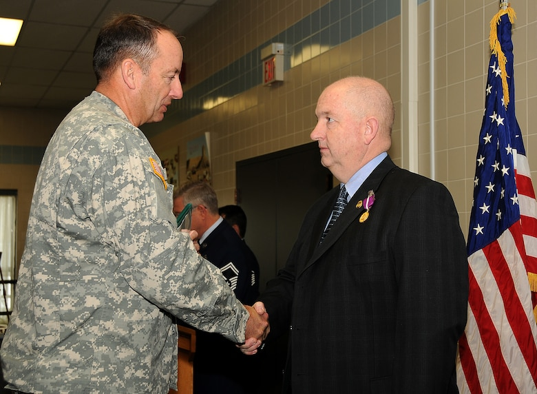 Maj. Gen. Brian L. Tarbet, The Adjutant General of the Utah National Guard, awards Brig. Gen. Scott Harrison the Joint Medal of Merit for his service during a retirement ceremony on January 9 at the Utah Air National Guard Base. General Harrison was the deputy commander of Joint Forces Headquarters, Utah NG, and officially retired from the Guard after 35 years.   U.S. Air Force Photo by: Staff Sgt. Emily Monson (RELEASED)