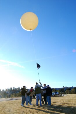 """Air Force Academy cadets prepare to launch a weather balloon named """"Roswell II"""" from the Academy's Stillman Parade Field Jan. 10, 2010. The cadets launched the balloon as part of a Space Club experiment after notifying officials at Denver International and Colorado Springs airports. (U.S. Air Force photo/Staff Sgt. Don Branum)"""