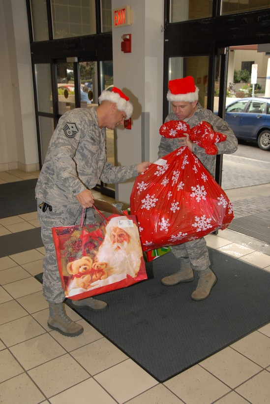 """1st Sgt. Richard Parker, 134th Security Forces Squadron, and Tech. Sgt. James Bohanan, 134th Wing Staff, sort through Christmas gifts for the East Tennessee Children's Hospital.  The Tenth Anniversary of the """"Santa Cop"""" program was a record year bringing in over $18,000.  (Air National Guard Photo by Tech. Sgt. Kendra Owenby)"""