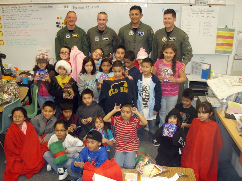 BOULDER, Colo. -- Volunteers from 460th Operations Group Detachment 1 pose with second-graders from Alsup Elementary in Commerce City, Colo. Dec. 17, 2009, after their gift drive. The volunteers raised $3,600 for blankets, sweatshirts and toys for each student as well as school supplies, playground equipment and a $250 gift card for the teachers. (U.S. Air Force photo)