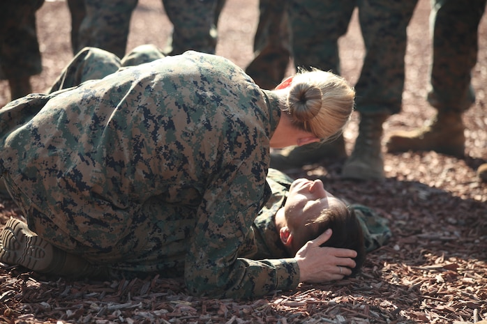 Petty Officer 1st Class Sarah Reed, a Combat Lifesaver Course instructor, checks for breathing on a simulated casualty during the CLS course hosted by the Advisor Training cell at Camp Pendleton, Nov. 16.  The CLS course equips Marines with fundaments to treat combat casualties.
