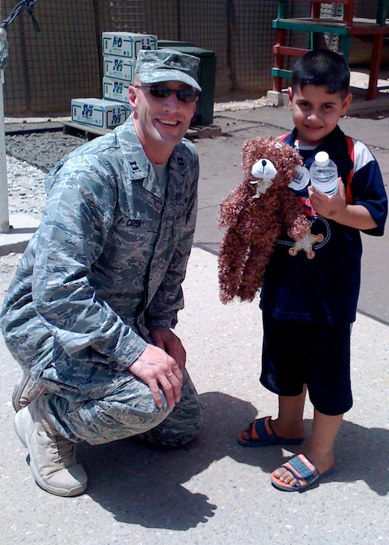 Chaplain (Capt.) Curt Cizek hands out water and a stuffed animal to a local Iraqi boy while deployed to Camp Bucca.  Chaplain Cizek attended to the spiritual needs of the base personnel ranging from all five services, civilian contractors, and third country nationals.