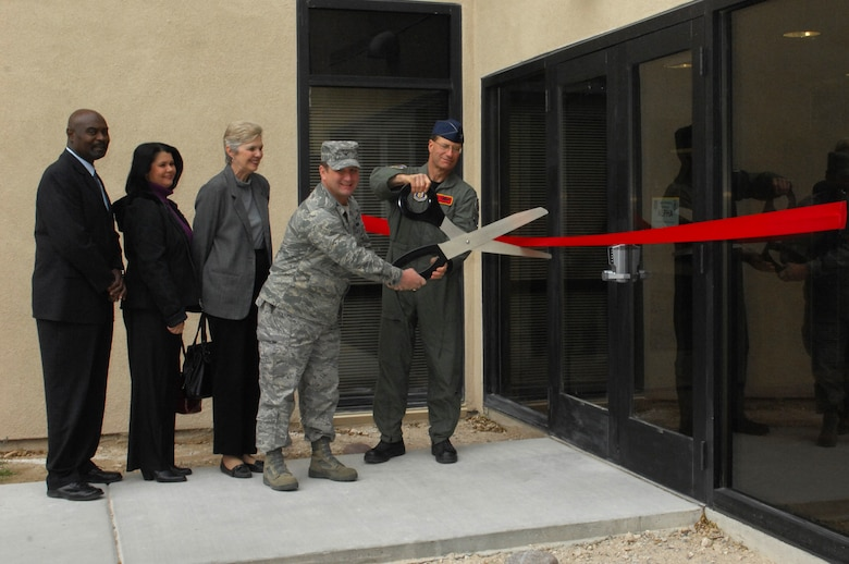 (Right to left) Col. Herman Brunke, 926th Group commander, and Col. Steven Winklmann, 99th Air Base Wing vice commander, cut the ribbon signifying the official opening of the 926th GP's headquarters building, while observed by Ms. Margot Allen of Senator Ensign's office, Ms. Roxane Unverrich of Congresswoman Berkley's office and Mr. Robert Sharp of Senator Reid's office. The new facility, along with an adjacent building, houses all of the group's Nellis personnel in one location. (U.S. Air Force photo/Staff Sgt. Erin Worley)