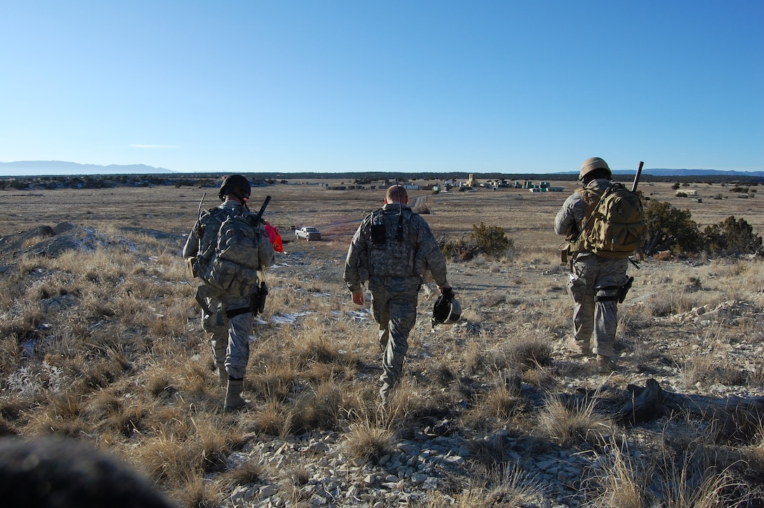 The Joint Terminal Attack Controllers walk to the village after calling in F-16 air strikes.  The two villages on the Airburst Range are created and built by its twelve unit members.