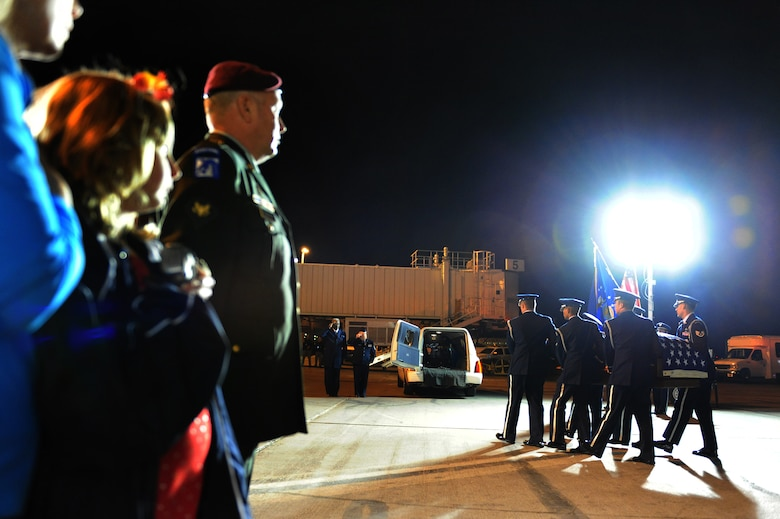 """LAS VEGAS-- Russell Goodman (in uniform), along with his sisters, Christine and Deborah, look on as members of the Nellis Air Force Base Honor Guard provide a dignified transfer for the remains of their father, Maj. Russell C. Goodman, a U.S. Air Force pilot that was killed in action during the Vietnam War, from a Hawaiian Airlines flight at McCarran International Airport Jan. 12. Major Goodman served as the narrator for the U.S. Air Force Air Demonstration Squadon """"Thunderbirds"""" from 1964-65 and was declared missing in action after his aircraft was hit by a surface-to-air missile Feb. 20, 1967, while on a combat mission over North Vietnam. At the time of his loss, Major Goodman was still assigned to the Thunderbirds and was flying with the U.S. Navy on an exchange program. Funeral services for Major Goodman will take place at the Thunderbirds Hangar on Nellis AFB at Jan. 14. He is to be buried in Alaska at a date determined by his family. (U.S. Air Force Photo by Staff Sgt. William P. Coleman/RELEASED)"""