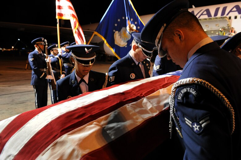 """LAS VEGAS -- Members of the Nellis Air Force Base Honor Guard provide a dignified transfer for the remains of Maj. Russell C. Goodman, a U.S. Air Force pilot that was killed in action during the Vietnam War, from a Hawaiian Airlines flight at McCarran International Airport Jan. 12. Major Goodman served as the narrator for the U.S. Air Force Air Demonstration Squadon """"Thunderbirds"""" from 1964-65 and was declared missing in action after his aircraft was hit by a surface-to-air missile Feb. 20, 1967, while on a combat mission over North Vietnam. At the time of his loss, Major Goodman was still assigned to the Thunderbirds and was flying with the U.S. Navy on an exchange program. Funeral services for Major Goodman will take place at the Thunderbirds Hangar on Nellis AFB at 11 a.m. Jan. 14. He is to be buried in Alaska at a date determined by his family. (U.S. Air Force photo by Tech. Sgt. Michael R. Holzworth/RELEASED)"""