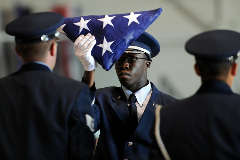NELLIS AIR FORCE BASE, Nev.-- Airman 1st Class Erastus Odongo of the Nellis Honor Guard dresses the flag during the repatriation and funeral ceremony in honor of Maj. Russel C. Goodman at the Thunderbird hanger on Nellis AFB, Jan. 14, 2010. Maj. Goodman served as the narrator for the U.S. Air Force Thunderbirds from 1964-65 and was declared Missing-In-Action after his aircraft was hit by a surface-to-air missile in Feb. 1967, while on a combat mission over North Vietnam. (U.S. Air Force photo by Tech. Sgt. Michael R. Holzworth)