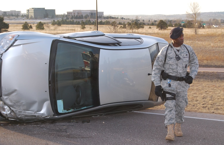 Staff Sgt. Ronald Young directs traffic around a vehicle rollover accident on Briargate Parkway near Interstate 25 in Colorado Springs, Colo., Jan. 14, 2010. No one was injured in the accident. Sergeant Young is assigned to the Air Force Academy's 10th Security Forces Squadron.The Academy's fire department and 10th SFS work alongside Colorado Springs and Colorado authorities to respond to accidents along the Interstate 25 corridor near the Academy. (U.S. Air Force photo/Staff Sgt. Don Branum)
