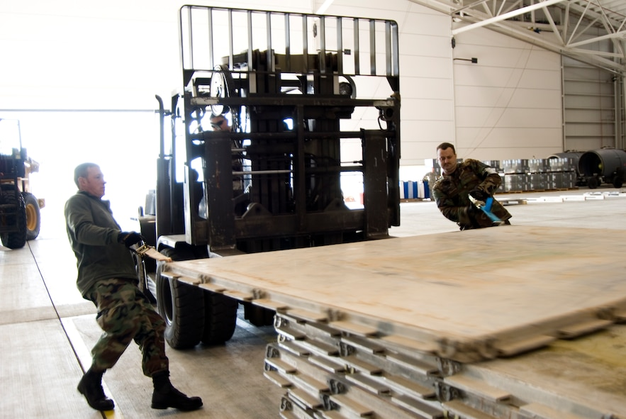 Tech. Sgt. Jody Miller and Tech. Sgt. Darren Rebuck slide pallets onto a forklift on January 15, 2010 at the 167th Airlift Wing. The air base in Martinsburg, W.Va, was transformed Janunary 14 into a staging area for more than 332,000 pounds of supplies bound for the airport at Port-au-Prince, Haiti. Hundreds of thousands of pounds more are expected to be palletized at the base for shipment to Haiti in the coming days. (U.S. Air Force photo MSgt Emily Beightol-Deyerle)