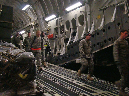 Members of the 621st Contingency Response Wing step down a C-17 Globemaster III cargo hatch Jan. 14, 2010, at the Toussaint L'Ouverture International Airport, Haiti. The 21 passengers and 44 tons of cargo were sent to Haiti on a 305th Air Mobility Wing C-17 from Joint Base McGuire-Dix-Lakehurst, N.J., to support relief operations in response to a devastating earthquake in the area. (U.S. Air Force photo/Tech. Sgt. Denise Johnson)