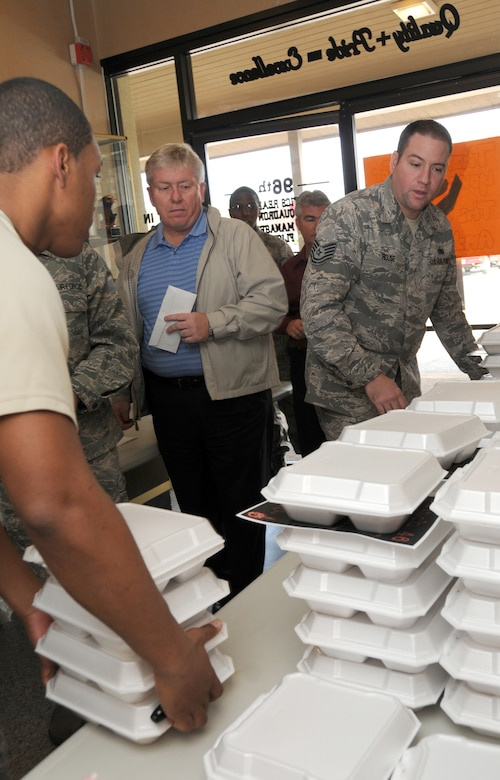 Tech. Sgt. Brent Rouse, 96th Logistics Readiness Squadron, helps carry out orders of pulled pork sandwiches for a fundraiser to raise monies for fellow a Airman. The proceeds raised will help offset additional costs the family is incurring while Tech. Sgt. Olafsen undergoes treatment to for leukemia at Sacred Heart Hospital in Pensacola, Fla. The  (U.S. Air Force photo/ Staff Sgt. Stacia Zachary)
