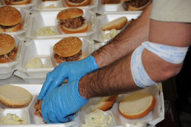 Master Sgt. Matthew Renner, 96th Logistics Readiness Squadron Fuels Flight, prepares pulled pork sandwiches after donating blood in Tech. Sgt. Eric Olafsen's name.  Sergeant Olafsen is fighting leukemia at Sacred Heart Hospital in Pensacola, Fla. The fundraiser will help raise money needed to offset additional costs the family is incurring while Sergeant Olafsen undergoes treatment. Sergeant Renner once supervised the sergeant. (U.S. Air Force photo/ Staff Sgt. Stacia Zachary)