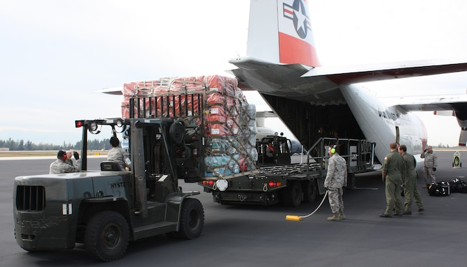 Reservists from the 70th Aerial Port Squadron load equipment for the South Florida Urban Search and Rescue FL-TF 2 Team for deployment to Haiti on a U.S Coast Guard C-130 on Jan. 14, 2010. (U.S. Air Force photo/Ian Carrier)