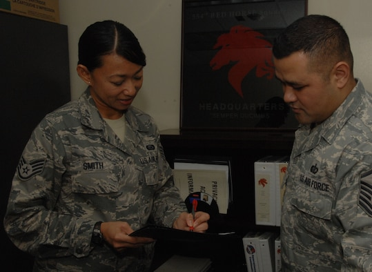 ANDERSEN AIR FORCE BASE, Guam - Staff Sgt. Elsie Smith, 554th RED HORSE Squadron, reviews documents with Master Sgt. Norbert Mendiola, 554th RED HORSE guard liaison here Jan. 15. Sergeant Smith, originally from the 254th Air Base Group here, was named 'Top Performer' for the 554th RHS by Master Sgt. Wesley Willand, 544th RHS first sergeant. (U.S. Air Force photo by Senior Airman Shane Dunaway)