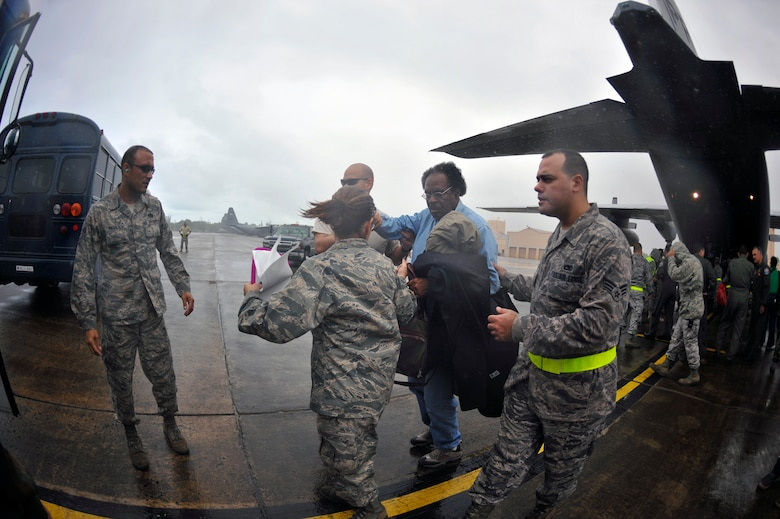 Airmen from the Puerto Rico Air National Guard's 156th Airlift Wing assist U.S. citizens after being transported by a C-130E Hercules aircraft Jan. 17, that landed in San Juan, Puerto Rico. The American citizens were evacuated from Haiti where Airmen are playing an active role in support of the relief effort there in the aftermath of a devastating earthquake. (U.S. Air Force photo/Staff Sgt. Desiree N. Palacios)