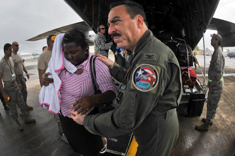 Col. Carlos Quinones assists a U.S. citizen living in Haiti off of a C-130E Hercules aircraft Jan. 17, that landed in San Juan, P.R. Colonel Quinones is the 156th Wing Commander. Airmen from the Puerto Rico Air National Guard's 156th Airlift Wing are working around the clock in support of the relief effort in Haiti in the aftermath of a devastating earthquake. (U.S. Air Force photo/Staff Sgt. Desiree N. Palacios)