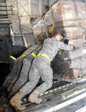 Air transportation specialists with the 437th Aerial Port Squadron at Charleston Air Force Base, S.C., work together Jan. 18, 2010, to load a pallet of food onto a C-17 Globemaster III from McChord AFB, Wash.  The pallet of food is part of a 116,000-pound shipment of food and water to aid victims of the recent earthquake in Haiti. (U.S. Air Force photo/Staff Sgt. Daniel Bowles)