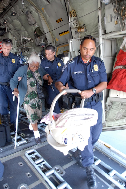 HOMESTEAD AIR RESERVE BASE, Fla. - U.S. Customs and Border Protection agents help and elderly Haitian lady and a baby from a C-130 aircraft assigned to the Minnesota Air National Guard. All personnel brought to Homestead ARB from Haiti must go through a Customs and Border Protection enforcement examimantion. (Air Force Photo/Master Sgt. Chance Babin)