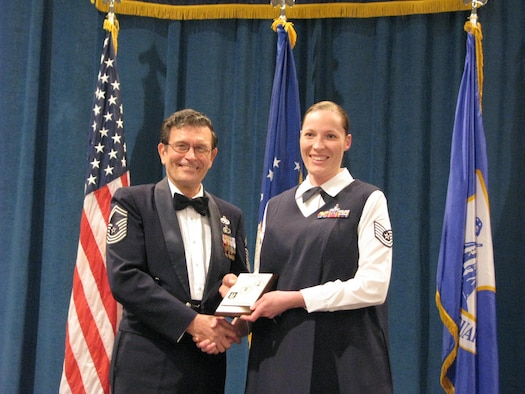 Technical Sgt Sarah Johnson receives her diploma from Chief Master Sgt (Ret) Lynn Alexander at a Non-Commissioned Officer graduation ceremony at McGhee Tyson Air National Guard Base, TN on Dec. 15.  Johnson was among 11 students from the Texas Air National Guard's 149th Fighter Wing and 273 Information Operation Squadron participating in an Air National Guard satellite NCO professional education course where students take a portion of their courses locally and then conclude with a 17-day in-residence course at McGhee Tyson.