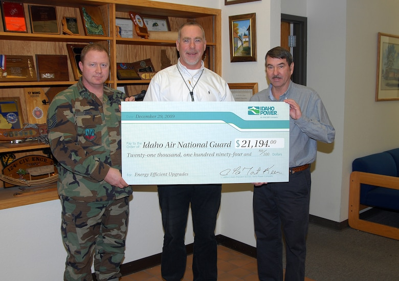 Mr. Dan Smith, Energy Efficiency Representative for Idaho Power, presents a check to Mr. Scott Busmann and Tech. Sgt. Travis Jones of the 124th Civil Engineer Squadron Dec. 29. The check represents money credited to the 124th Fighter Wing's electric account for energy efficiencient upgrades to facilities on Gowen Field. (Air  Force photo by Master Sgt. Tom Gloeckle)